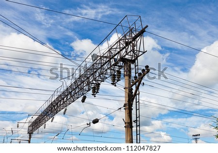 Forefront of a railway catenary with a blue sky - stock photo