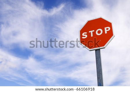 forefront of a stop sign with a cloudy sky - stock photo