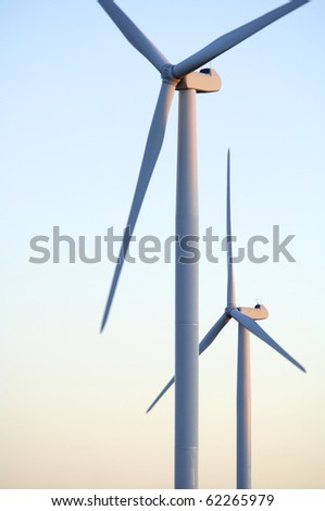 foreground at sunset two windmills with clear sky - stock photo