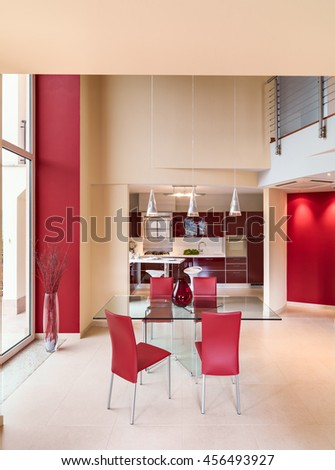 foreground of a modern glass dining table with red leather chairs overlooking on the purple kitchen whose floor is made of marble - stock photo