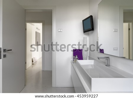 foreground of a washbasin in the modern bathroom overlooking on the living room - stock photo