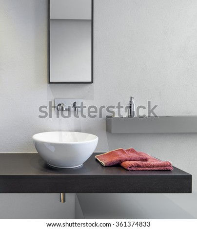 foreground of washbasin on the wooden worktop in the modern bathroom - stock photo