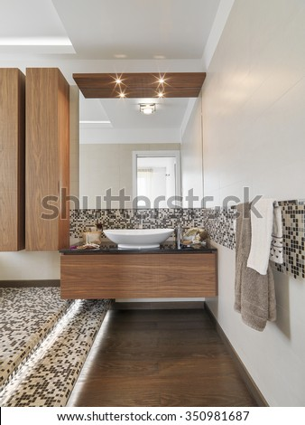 foreground of wood furniture with washbasin and wood floor in the modern bathroom - stock photo