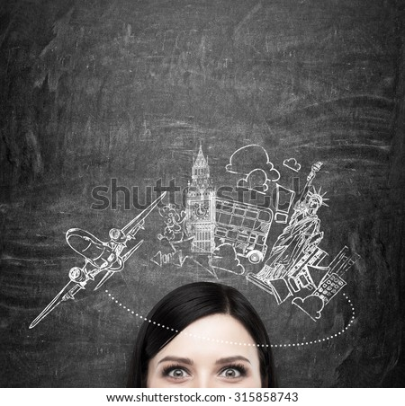Forehead of brunette lady who thinks about travelling. New York and London sketches are on the black chalkboard. The concept of anticipation of the adventure. - stock photo