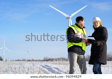 Foreman and engineer in snow winter field with wind turbines in background - stock photo