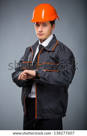 Foreman builder looks at his watch - stock photo