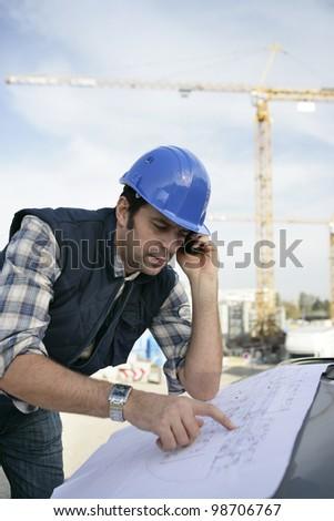 Foreman checking plan - stock photo