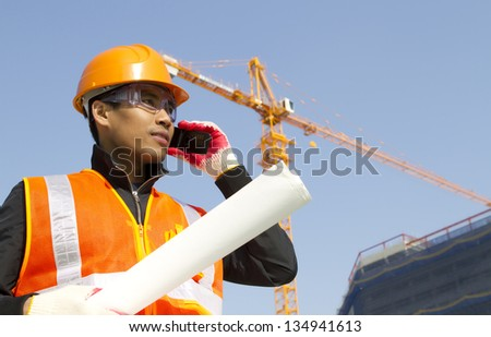 Foreman construction talking in mobile phone with crane in background - stock photo