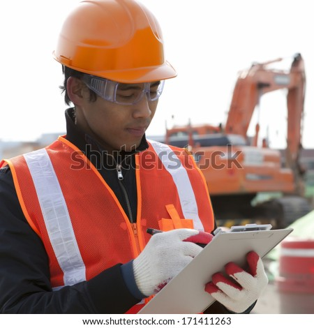 Foreman construction writing on clipboard standing beside excavator on location site - stock photo