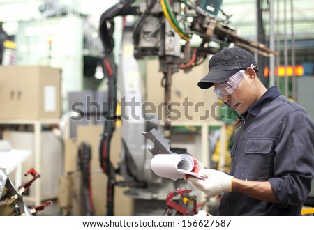Foreman in a factory checking quality of work  - stock photo