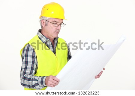 Foreman looking at plans - stock photo