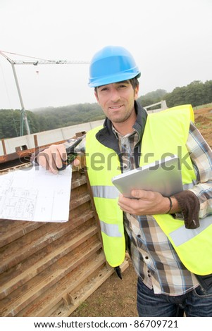 Foreman on building site with walkie-talkie - stock photo