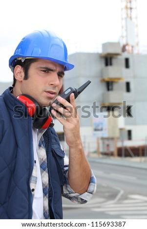 Foreman on construction site giving orders via radio - stock photo