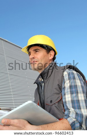 Foreman on industrial site with tablet - stock photo