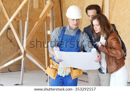 Foreman shows house design plans to a young couple - stock photo