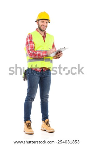 Foreman taking a notes. Smiling construction worker in yellow helmet and lime waistcoat posing with a clipboard. Full length studio shot isolated on white. - stock photo