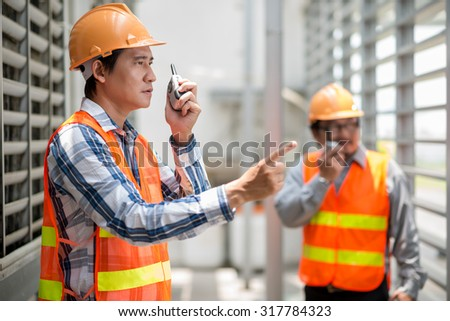 Foreman talking on walkie-talkie at the construction site - stock photo
