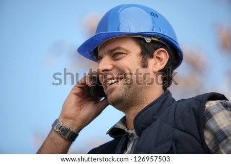 Foreman talking to colleagues via radio - stock photo