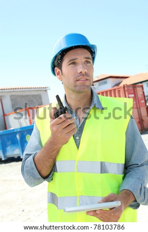 Foreman using walkie-talkie on construction site - stock photo