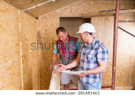 Foreman Wearing White Hard Hat with Building Plans Monitoring Worker Inside Unfinished Frame of New Home - stock photo