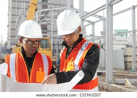 Foreman with safety vest discussion under construction - stock photo