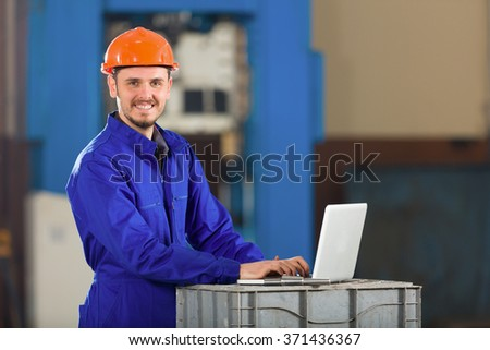 Foreman working with laptop in factory. - stock photo