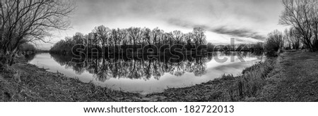 Forest island reflection on water- panoramic landscape black and white - stock photo