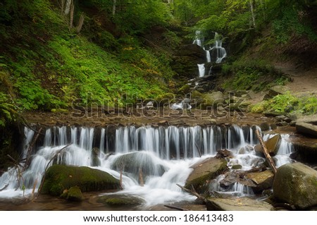 Forest landscape with beautiful waterfall on a mountain river. Cascades cold stream. Beech forest. Carpathians, Ukraine, Europe - stock photo