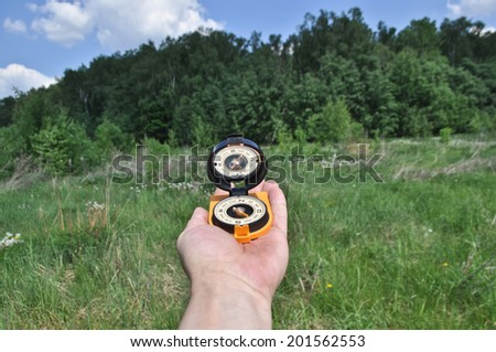 Forest, may, walk in the woods. Compass in hand, against the background of the forest. - stock photo