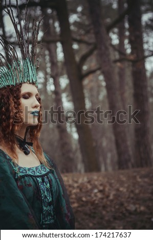 forest nymph in green dress with closed eyes - stock photo