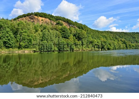 Forest trees reflecting in river water in sunny summer day near Fumay in Ardennes, France - stock photo