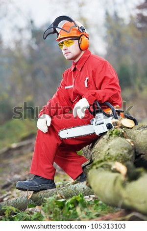 Forest woodcutter lumberjack Worker in protective safety work wear With Chainsaw - stock photo