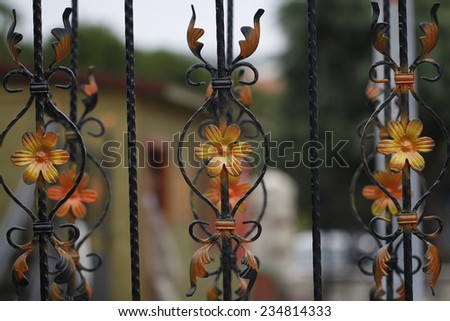 Forge Detail / Part of a wrought iron fence with yellow flowers / design iron gate details - stock photo