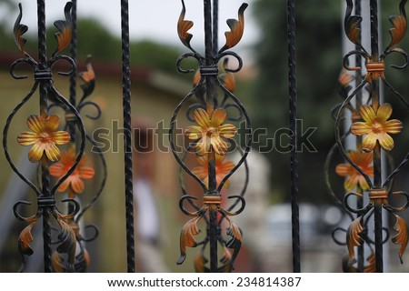 Forge Detail / Part of a wrought iron fence with yellow flowers ,/ design iron gate details - stock photo