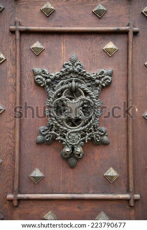 Forged old doorknob with a pattern - stock photo