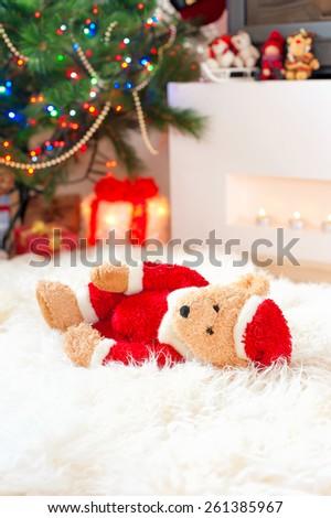 Forgotten gift. Santa teddy bear toy lie on sheepskin rug near illuminated christmas tree. - stock photo