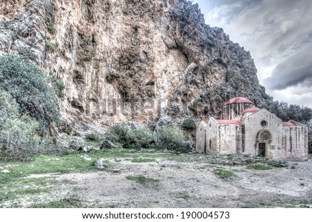 Forgotten 14thC church on the way to Agiogfarago in Crete, Greece with weathered frescos of saints destroyed by humidity on the exterior walls standing under a steep rocky cliff, HDR image - stock photo