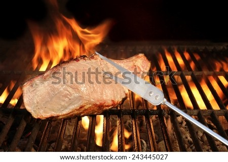 Fork and Grilled Meat on the BBQ Grill. Flames of Fire on the Background - stock photo