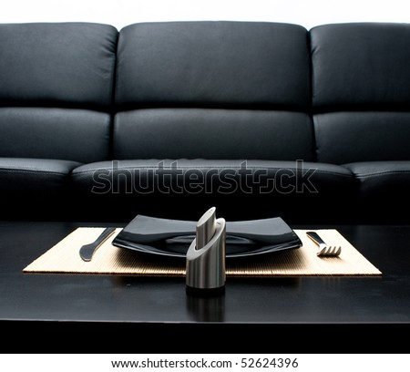 Fork and knife besides a square black plate - stock photo