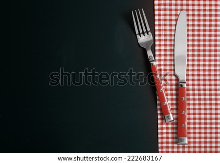 Fork and Knife on Checked Table Cloth at Black Table. - stock photo