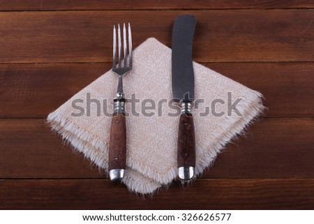Fork and knife on napkin on wood background - stock photo