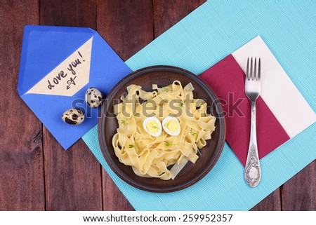 Fork and plate. Plate with egg pasta on the table. Love letter on the table. Love you. Hearty and delicious lunch on the table. Brown earthenware dish with pasta. - stock photo