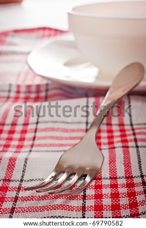 Fork and plates on checkered red tablecloth - stock photo