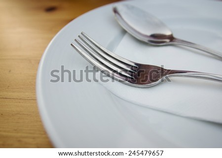 fork and spoon with white plate on wood table - stock photo