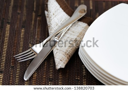 fork knife and empty plates on the background of brown material - stock photo