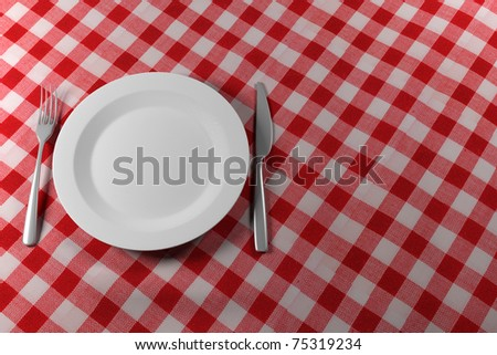 Fork Knife and Plate isolated on a red table cloth - stock photo