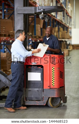 Fork Lift Truck Operator Talking To Manager In Warehouse - stock photo
