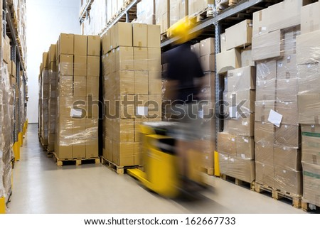 Fork lift with operator working in warehouse - stock photo
