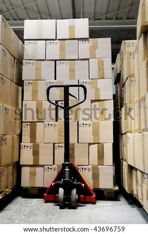 fork pallet truck stacker in warehouse in front of cardboard boxes - stock photo