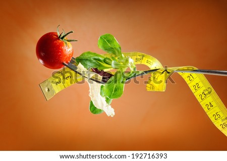 fork, salad and tape, nutritional diet concept with brown background - stock photo